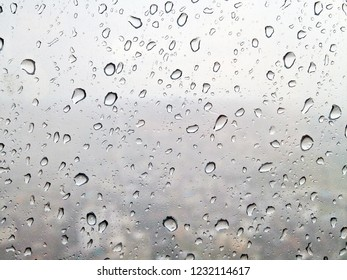 Rain drops on window glasses surface while heavy rain that seeing in blur background