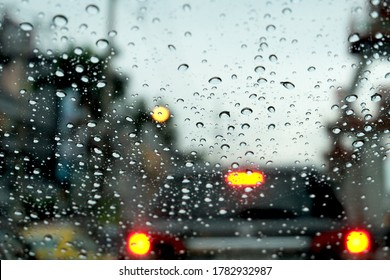 Rain drops on window glasses surface with cloudy background . Natural Pattern of raindrops isolated on cloudy background. Traffic jam in rainy day with raindrops on car glasses. in bangkok.
