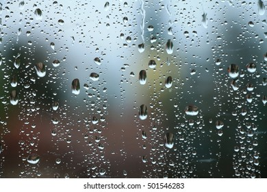 Rain drops on window with house and church in background