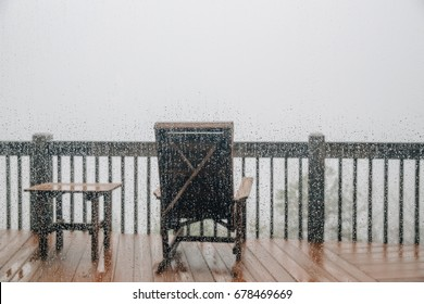 Rain drops on the window over blurred patio background with free space