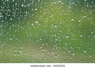 Rain drops on a window pane,  green blurry background