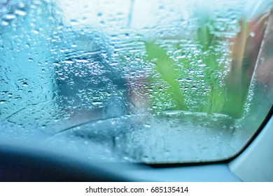 Rain drops on the windshield during the evening.Windshield with rain drops.Traffic is heavy and rain is falling.