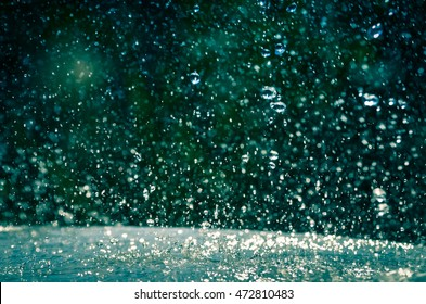 Rain drops splashing on a table in the garden rainy day background