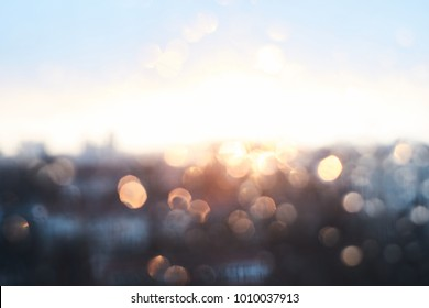 Rain drops texture on window glass with stunning vintage blue violet sunset light abstract blurred cityscape skyline bokeh background. Soft focus