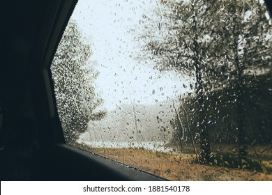 Rain drops through a car window in the middle of the dark dense forest, rainy and cloudy day in the mountains foggy background including a lake and tall trees, nostalgic mood