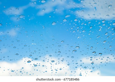 Rain drops, water drops of rain on a window glass. blurred lights city with sky clouds in rainy day, abstract blue background texture, view beautiful from outside window
