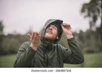 Rain drops. Young man in a green coat catching rain drops