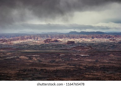 Rain is falling from the dark storm clouds in the distance, at the Needles Overlook in the Canyon Rims Recreational Area near Monticello, Utah.