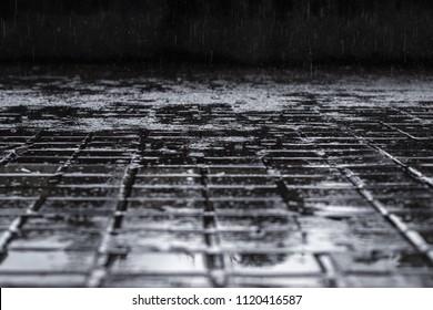 Rain falling down a urban outdoor city squared floor ground