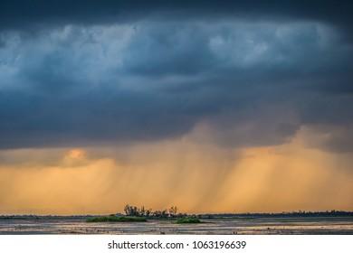 The rain falls over a small island on the lake.