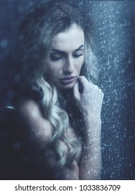 Rain. Female portrait, beauty young woman behind the window with water drops