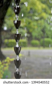 Rain is flowing down a Japanese rain chain. Each cup is designed like a flower. Heavy drops of rain are clearly visible. The greenery and path of an out-of-focus park are in the background.