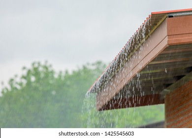 Rain flowing down from the roof house in rainy season