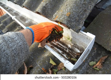 Rain Gutter Cleaning from Leaves in Autumn with hand.  Roof Gutter Cleaning Tips. Clean Your Gutters Before They Clean Out Your Wallet. Step by Step. Gutter Cleaning.