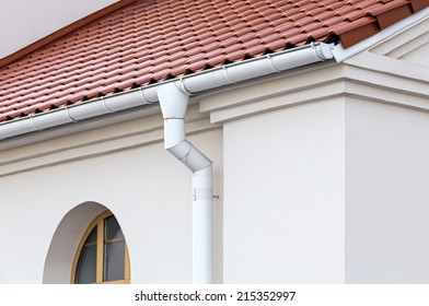 Rain gutter and downspout on wall of house