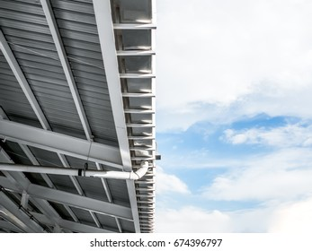 Rain gutter of factory against blue sky. Metal roof industrial design architecture.