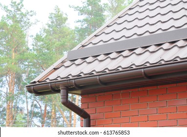Rain Gutter Pipeline System Installation. Roofing Construction. Rain gutter system and roof protection from snow (Snow guard). Home Guttering, Gutters, Guttering & Drainage Pipe Exterior.
