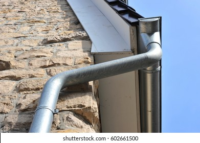 Rain gutter, rainwater pipe at a new tiled Roof