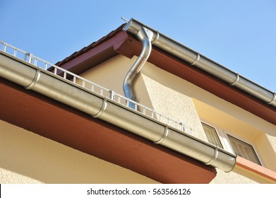 Rain gutter, rainwater pipe and snow guard on a tiled Roof