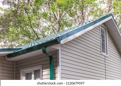 rain gutter system and tiled roof against green trees background
