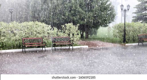 Rain and hail on a summer day. Large puddles on the sidewalk during heavy rain. Heavy rain with snow and hail in the Park. Wet benches on the paved path. Spray from drops and bubbles in large puddles.