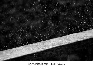 Rain hitting a wood plank during a storm with rain drops bouncing off of it.