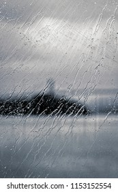 Rain leaves wet traces on the window. View of a bridge over a fjord in Norway.