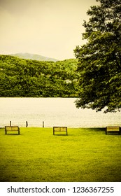 Rain and morning mist on the Wolfgangsee in Austria.  Small well-kept park with benches on a lawn near a lake in Austrian rural landscape. Vintage style