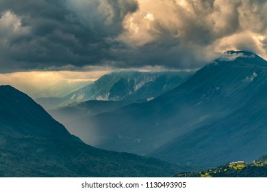 Rain in the mountains. Socha valley, Slovenia. Dramatic shot of heavy storm clouds, green meadows, and fog on the mountains