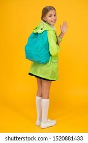 Rain is not hindrance. Schoolgirl raincoat going to school waving hand. Waterproof fabric for your comfort. Rainproof accessory. Waterproof clothes. Kid girl happy wear raincoat. Waterproof cloak.