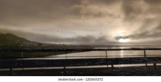 Rain on the bridge at sunset.