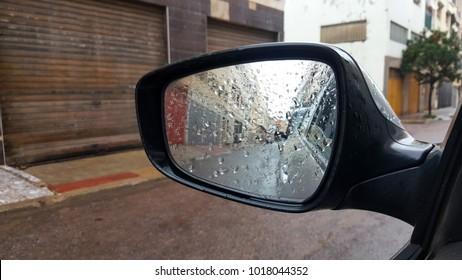 Rain on a car mirror. raindrops on car rear-view mirror