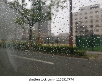 rain on car window in construction site. Heavy rain send muddy sediment into site. rain drops on car window. Rainy window.rain drops on windshield of car and background in several colors.