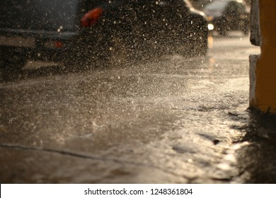 Rain on the street of a European city, wet pavement, ice-crusted ground, winter weather. Sleet forms an ice crust. Thaw, snow dripping from the roof onto the pavement.