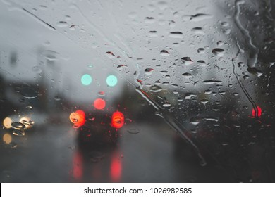 Rain on windshield of a car. Shot from inside. Raindrops. Car breaking lights and traffic lights in blurry background. Moody weather