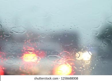 Rain, Rain on the windshield view from inside the car at road way traffic jam, rainy season, rainy storm (selective focus)