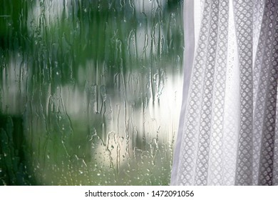 Rain outside the window. Smudges of water on the glass, curtains