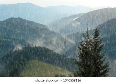 Rain over forest mountains. Misty mountain landscape hills at rainy weather. Summer Rain and sun.
