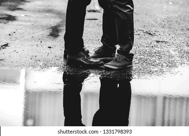 Rain puddle reflection of two people's legs.