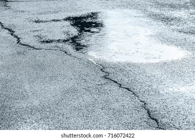 rain puddles on wet pavement with cracks in the city street