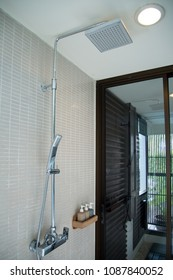 The rain shower in the bathroom with soft cream tiles