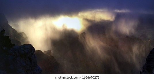 Rain shower curtains covering the Grand Canyon at sunset, creating crepuscular light rays and mist in the canyon's depths from Lipan Point.