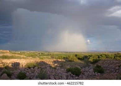 Rain storm over small desert town in distance