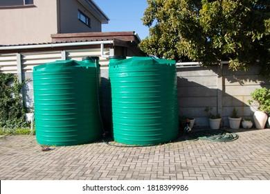 rain water catchment plastic tanks setup in backyard