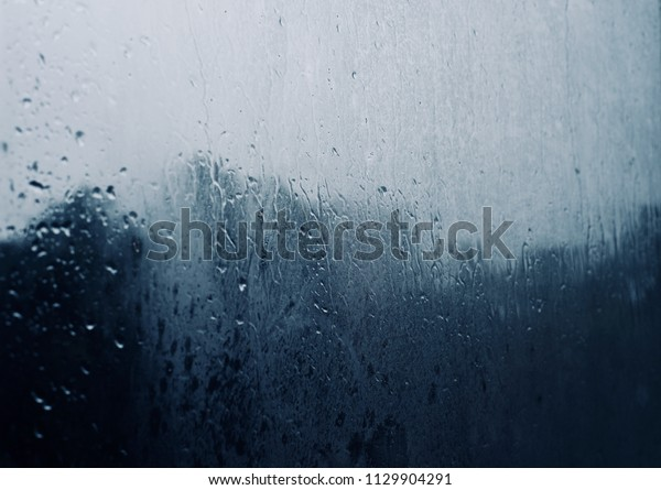 Rain water drops fallen on a glass of a window isolated blurry background photo