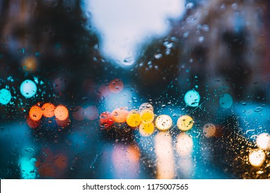 Rain Water Drops On Blue Glass Background In Night Or Evening Street Lights. Street  Bokeh Boke Lights Out Of Focus. Autumn Street Abstract Backdrop.