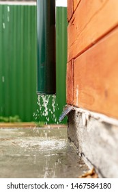 Rain water flows from a drainpipe to a concrete foundation, a wooden house, against a green fence. Close-up.