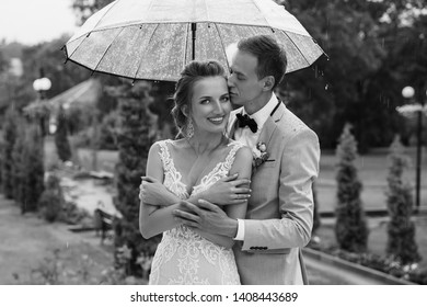 Rain at Wedding day. Happy Bride and Groom in the rainy weather are covered with a transparent umbrella