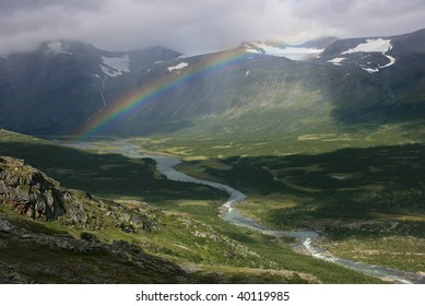 Rainbow above the river in a green arctic valley in the mountains of Sarek, Sweden