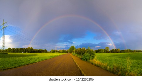 Rainbow after a thunderstorm over a road that stretches between fields on the horizon